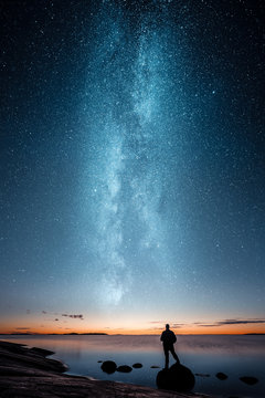 Silhouette of a man standing alone on a rock by a sea and looking at sunset and stars of the Milky Way