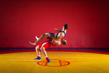 Two strong wrestlers in blue and red wrestling tights are wrestlng and making a  hip throw wrestling on a yellow wrestling carpet in the gym. Young man doing grapple.