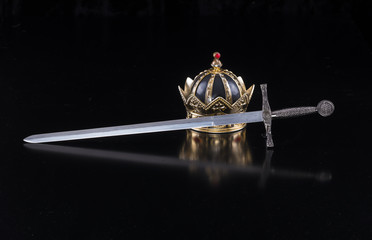 Medieval sword and crown on a black isolated background