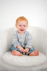 Kid sits on a white plush armchair