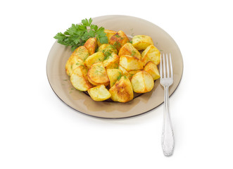 Fried potatoes on dark glass dish and fork