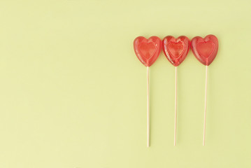 Three candy in heart shape on green background