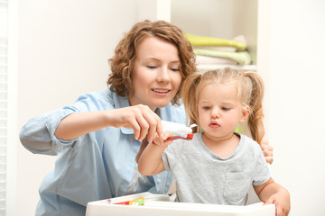 Mother teaching daughter to brush teeth in bathroom