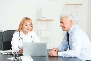 Female doctor consulting senior patient in clinic