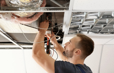 Male technician measuring voltage during repair of industrial air conditioner indoors
