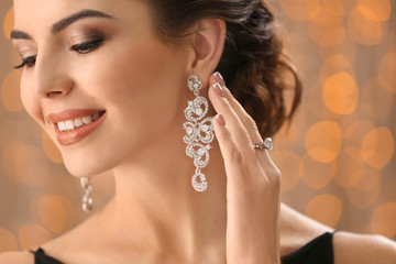 Beautiful young woman with elegant jewelry against defocused lights