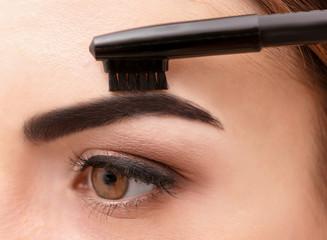 Young woman correcting shape of eyebrows, closeup