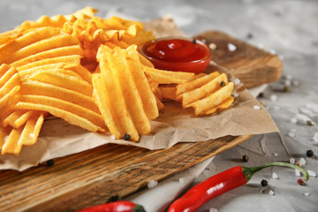 Crispy potato chips with chili pepper and sauce on wooden board, closeup