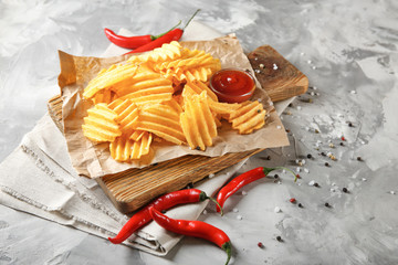 Crispy potato chips with chili pepper and sauce on wooden board