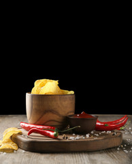 Bowl with crispy potato chips, chili pepper and sauce on wooden table against dark background