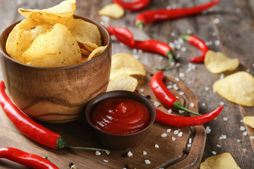 Bowl of crispy potato chips with pepper chili  and sauce on wooden table, closeup
