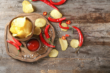 Bowl with crispy potato chips, chili pepper and sauce on wooden table, top view