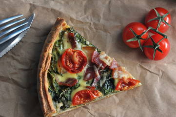 A piece of French classic pie quiche with spinach, bacon, cherry tomatoes, cheese. Next cutlery and cherry tomatoes. Background of kraft paper. View from above. Close-up.