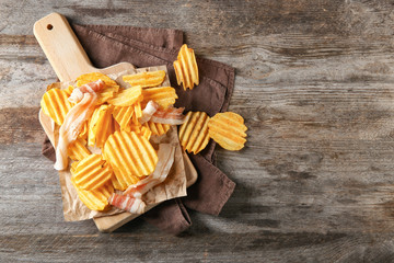 Crispy potato chips with bacon on wooden table, top view