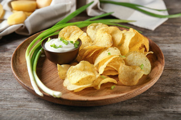 Crispy potato chips with green onion and sour cream on wooden plate