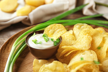 Crispy potato chips with green onion and sour cream on wooden plate, closeup
