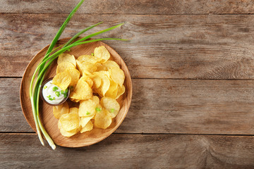 Crispy potato chips with green onion and sour cream on wooden plate, top view