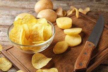 Bowl with crispy chips and raw potato on wooden table