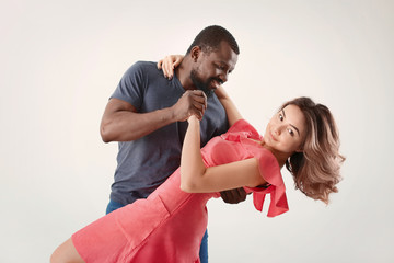 Cute interracial couple dancing against white background