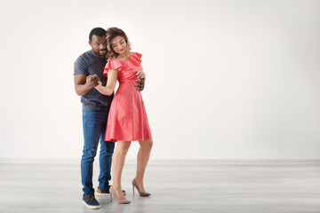 Cute interracial couple dancing in empty room