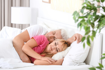 Mature couple hugging in bed. Romantic morning