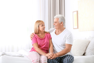 Mature couple sitting on bed. Romantic morning