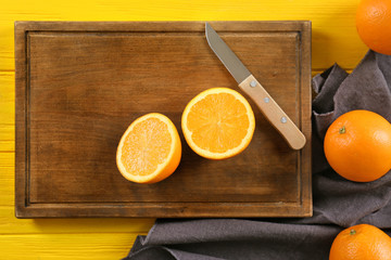 Wooden board and juicy ripe oranges on table, top view