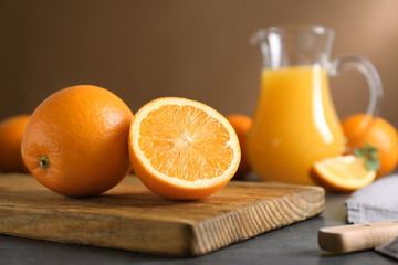 Wooden board with juicy ripe oranges on table