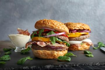 Tasty burgers on slate plate