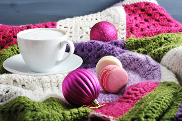 On a knitted multi-colored plaid white cup with cappuccino. Near two pastry macaroons. Two Christmas balls give the composition a Christmas mood. Close-up.