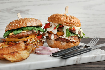 Tasty burgers and potatoes on marble board