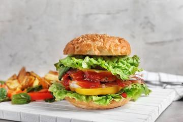 Tasty burger on wooden board