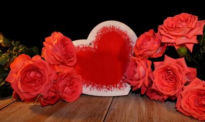 красивая розовая роза и фигурка сердца на черном фоне на деревянных досках