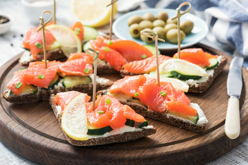 Canape sandwiches with salmon, cucumber and cream cheese. Closeup view