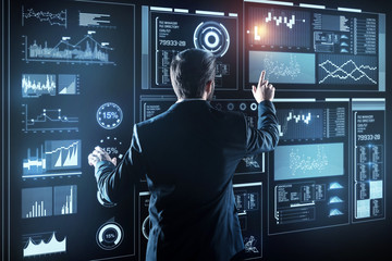 Comparing information. Calm clever attentive programmer standing in front of a futuristic device and touching its transparent screen while analyzing and comparing new important information