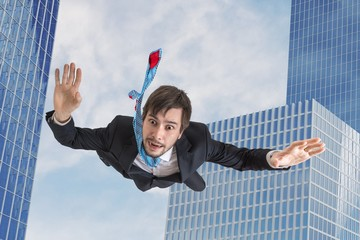 Young businessman falling down in free fall. Skyscrapers in background.