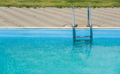 Close-up swimming pool with metal stairs outdoor in a private house