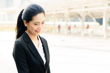 Portrait of a success Asian confident business woman smiling in the city. Ways to be happy at work concepts.