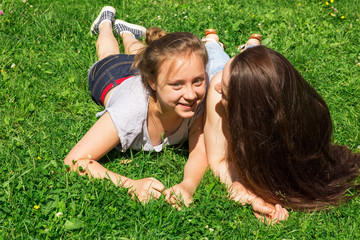 Two beautiful girls have fun on city park. Copy space.