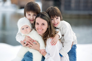 Beautiful mother in white dress and her cute children, three boys