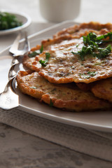 Vegetable pancakes with parsley on white plate
