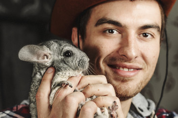 Portrait of a Cowboy. dark hair, jeans , plaid shirt. he holds the chinchilla animal