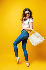 Beautiful young woman in sunglasses, white shirt, blue jeans posing with bag on the yellow background
