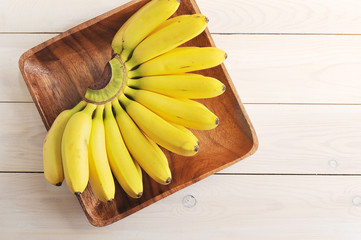 A bunch of ripe bananas on a square wooden plate. Light wooden background. View from above. Free space for text.