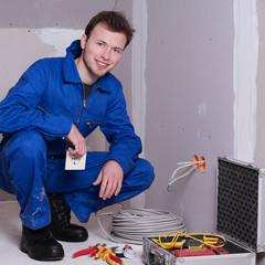 Elektriker auf einer Baustelle blickt in die Kamera