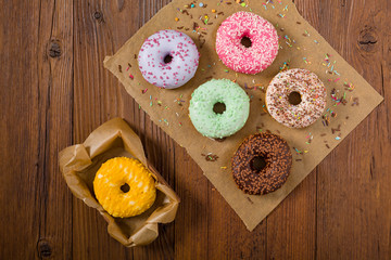 Colorful donuts on a wooden background.