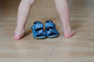 Contrast of barefoot children's legs and  shoes