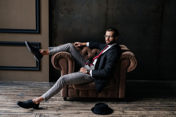 handsome elegant businessman posing in armchair, hat lying on floor near, loft interior Wall mural