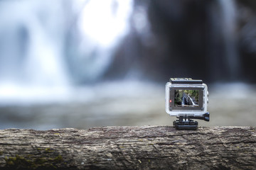 Action-cam on top of a brown tree with the waterfall behind.