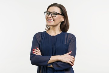 Positive business woman of middle age posing over white with arms crossed.